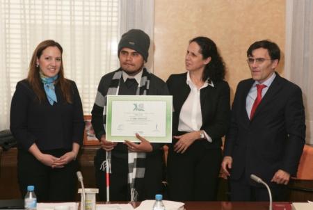 El ganador del Concurso 'FOAL y Yo' en la modalidad de audio, Ariel Ruiz, sostiene una placa acreditativa durante el último Patronato de FOAL acompañado por el presidente y la vicepresidenta de FOAL, así como de una representante de la Embajada de Paraguay en España