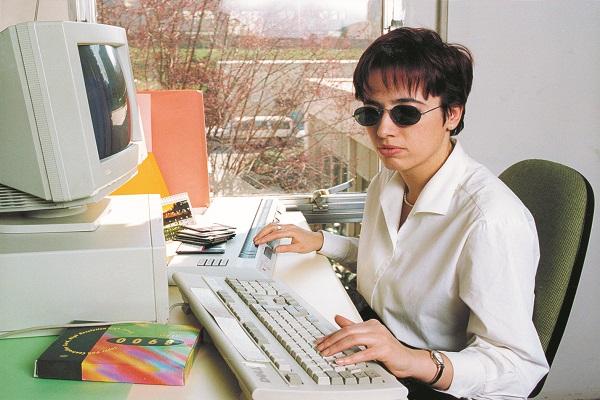 Una joven ciega en su puesto de trabajo con un ordenador y línea braille