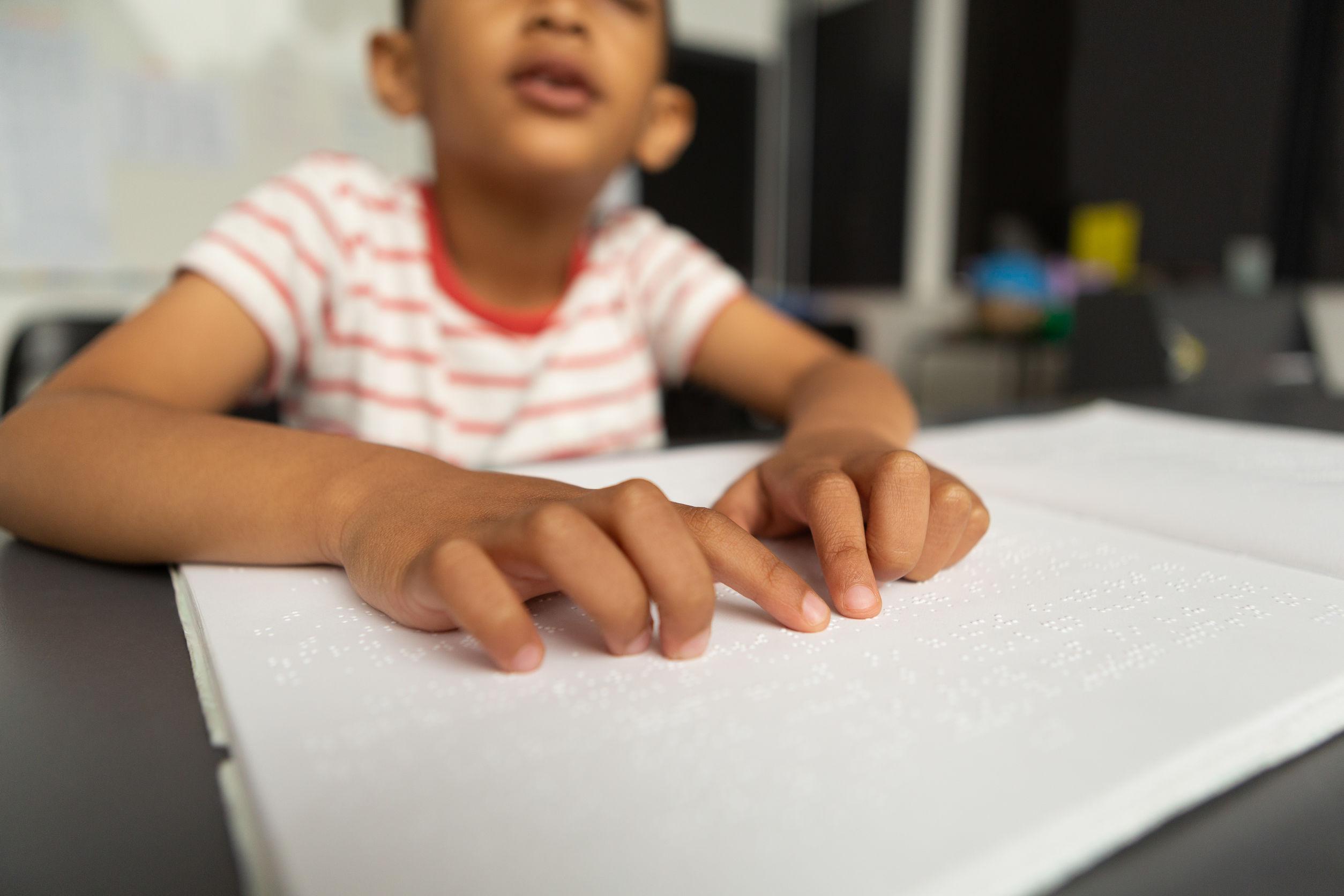 Un niño de unos 8 años lee en braille