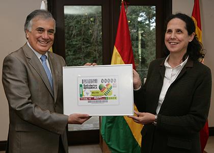 La directora de RRII de la ONCE, Ana Peláez, entrega el cupón enmarcado al embajador de Bolivia en España, Jorge Ramiro Tapia Sáinz