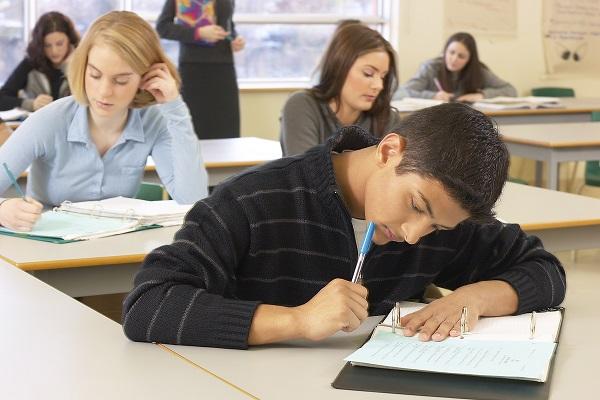Jóvenes estudiantes escribiendo en clase