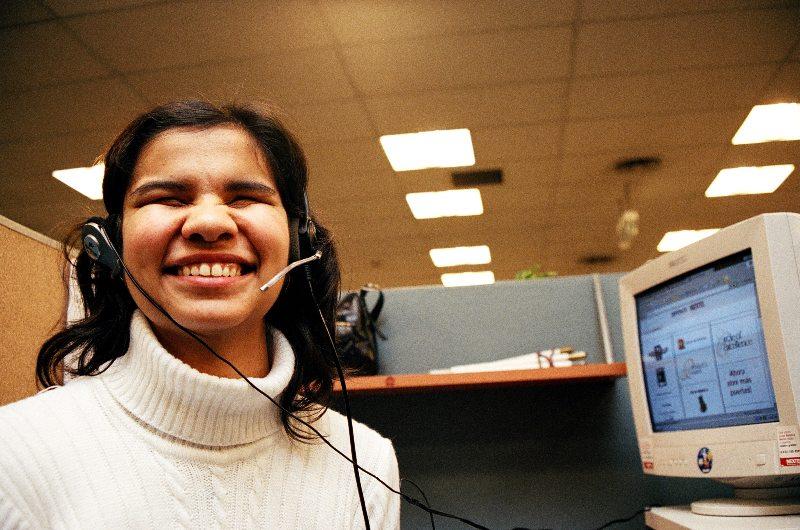 Una joven con discapacidad visual, en su puesto de trabajo frente a una computadora