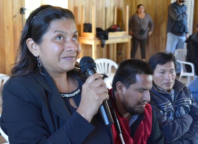 Una mujer con discapacidad visual habla con un micrófono junto a otras personas