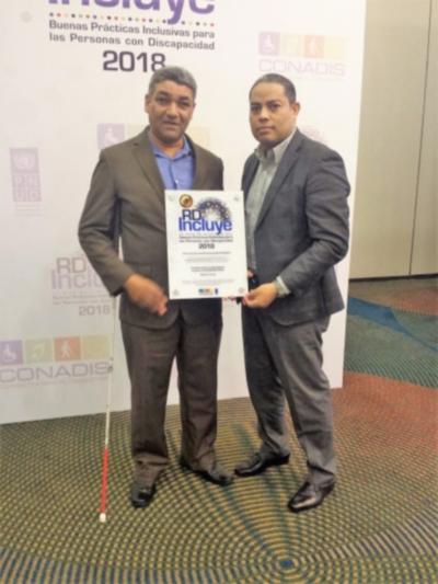 El presidente de la Federación Dominicana de Ciegos, Lino Delgado, posa con el premio junto al ex coordinador del Programa ÁGORA República Dominicana, Miguel González