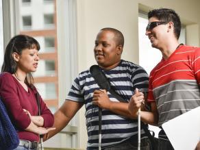 Tres personas con discapacidad visual de Costa Rica hablan amistosamente