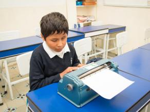 Niño mexicano escribe con máquina Perkins